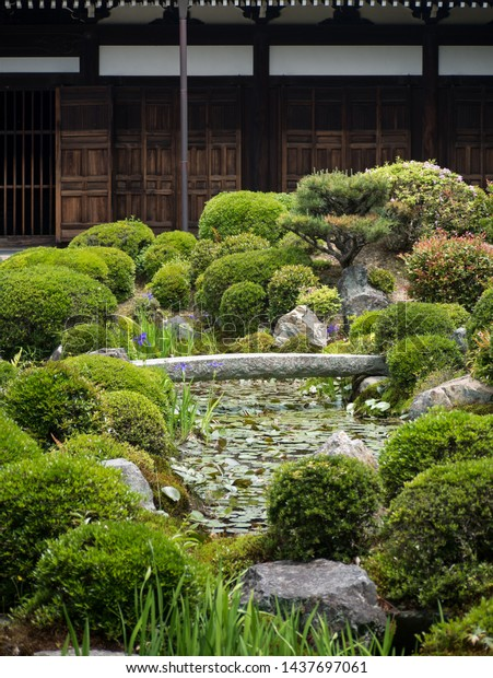 Small landscape garden with a water stream, stone bridges and water lilies at Kaizando hall of Tofukuji temple in Kyoto, Japan