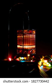 small lantern with a candle and some lights in the background