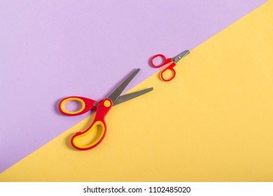 Small and large scissors with red handles on two-color paper background of lilac and yellow. Minimal style. Concept of education: from small to large, from simple to complex