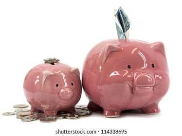 Small and larger piggy banks with coins and notes