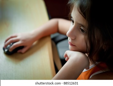 Small latin  girl working with a computer at home