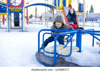 Small laughing child rides carrousel in winter
