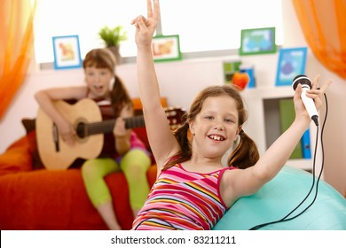 Small laughing girl with microphone, raising arms happily, friend playing guitar.?