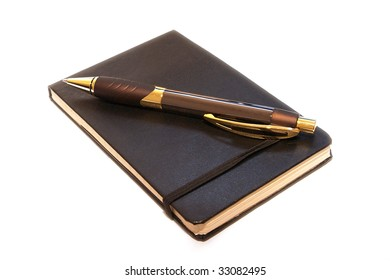 A small leather bound notebook with expensive pen laying on top of it against white