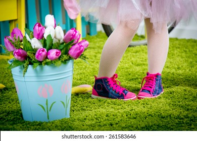 Small legs of the little girl in pink gym shoes
