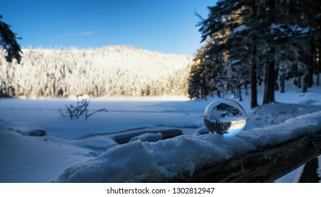 Small lens ball on frozen banister in winter close to lake