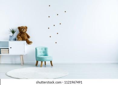 Petit fauteuil bleu clair pour enfant debout dans un intérieur de chambre blanche avec étoiles au mur, tapis blanc et placard avec livres, ours en peluche et plantes fraîches. Espace vide pour votre berceau