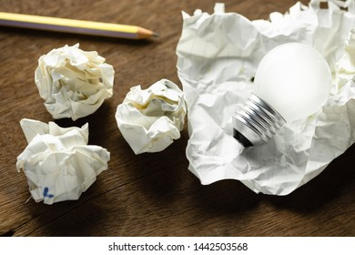 Small light bulb in crush paper with crumpled paper balls, create good writing idea