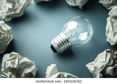 Small light bulb glowing in the group of crumpled paper balls, metaphor to success idea or learning from mistake concept