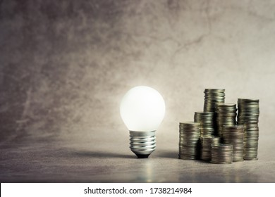 Small light bulb glowing with group of heap coins, small business concept, niche market plan, startup in limit budget, or smart finance concept