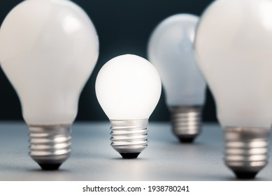 Small light bulb is glowing in the group of the big light bulbs, small business in competition idea, or coaching and success training concept