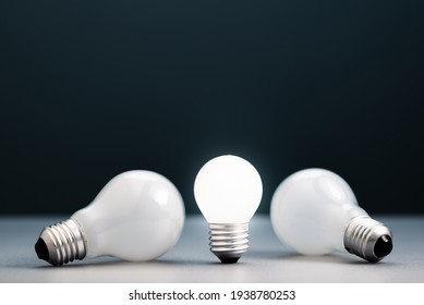 Small light bulb is standing and glowing while the big ones was laying down, advantage of small thing,  small business in competition idea, find a niche business