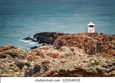 Small lighthouse on jagged cliffs by the sea. Kullaberg, Sweden.
