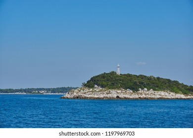Small lighthouse, sea sign on a small island in the blue Adriatic Sea off Vrsar, Croatia, in bright sunny weather and clear skies