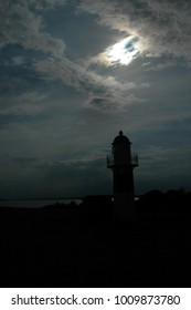 A small lighthouse seen in backlight with a sinister sky as background.
