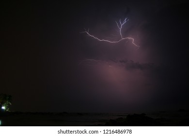 Small lightning strike in sky at clouds