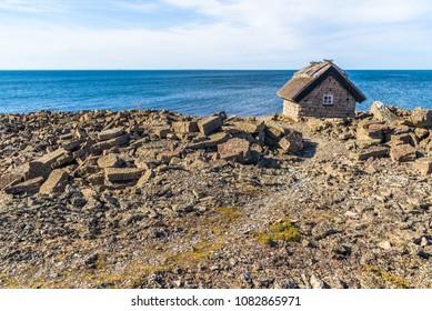 Small limestone cabin on the edge of a coastal limestone cliff on the island of Oland, Sweden.