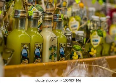 Small limoncello bottles for sale in a souvenir shop in Italy; typical Italian souvenir; lemon liquor