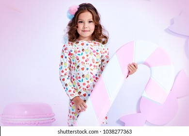 Small little girl beautiful lady curly hair child wear funny clothes dress socks boots cute face smile sweets baby shower party bar game room birthday hold big candy lollipop macaroons toy play fun.
