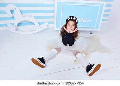 Small little girl sit on the floor beautiful lady curly hair child wear funny clothes skirt t-shirt hat beret cute face smile sweets baby shower party candy bar game room birthday fun happy play toy.