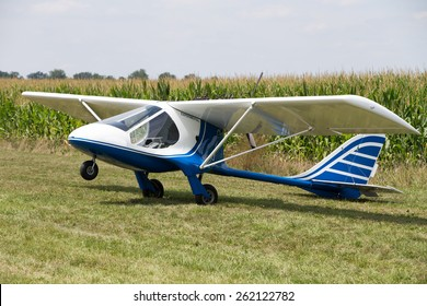 Small little single engine microlight experimental plane sitting in a field balance on its tail with the nose wheel in the air waiting for the pilot to return to counter the weight