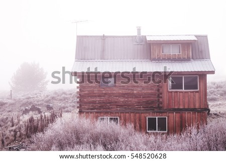 Small Log Cabin In Frozen Winter Landscape. Fog And Icy Bushes Surround A Compact  Cabin