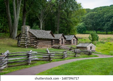 A small log cabin village under the shadow of some large trees with a split rail fence in the foreground.