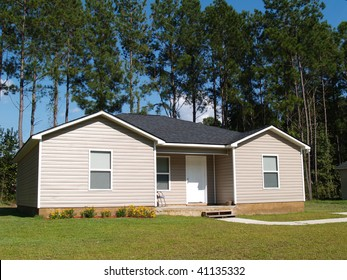 Small low income home with tan vinyl siding.
