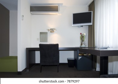 A small, but luxurious and modern styled hotel room with various appliances and features
