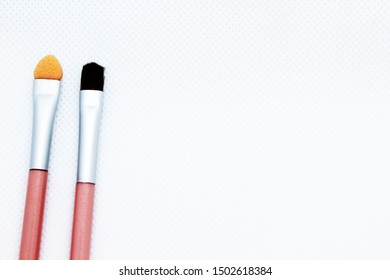 Small makeup brushes on a white background