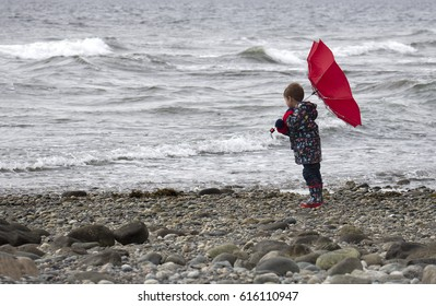 small male child at the beach holding his red umbrella against the wind.