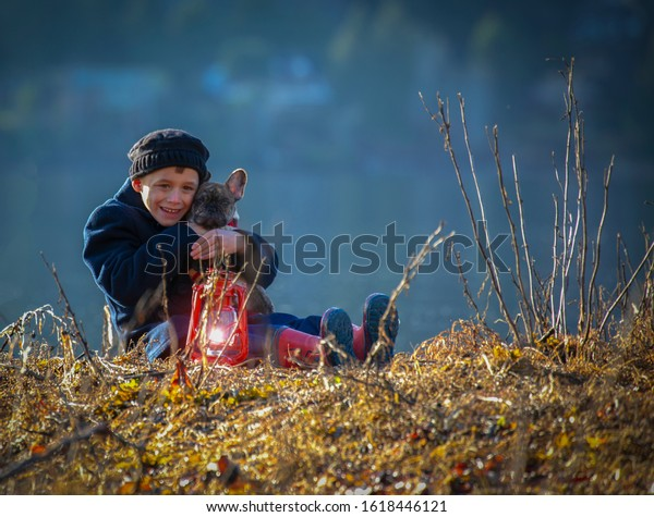 Small male child sitting by a lake holding a French Bull Dog puppy with an antique lantern.