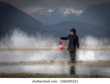Small male child standing at the beach holding a lit red lantern.