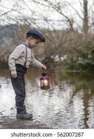 small male child standing near a rural pond holding a retro candle lit lantern.