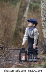 small male child standing on a forest trail bent over holding a candle lit lantern.