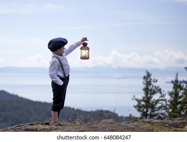 small male child standing on a hill overlooking the ocean holding a candle lit lantern.