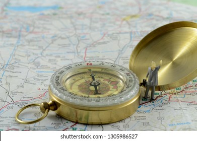 A small male figurine stands next to a compass on a map for navigational concepts.