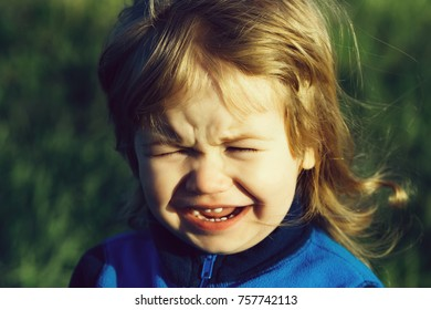 Small male kid with emotional face and blond curly hair squinting from sun outdoor on green background