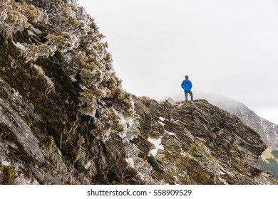 a  small man(hiker) with blue cloth is standing on the mountain cliff around white foggy sky in Mt.Hehuan, Taiwan at snow season.