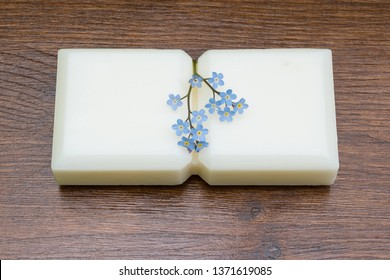 Small marseille soap isolated with flowers on wooden table in the foreground.foreground.