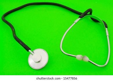 Small medical stethoscope on a green background
