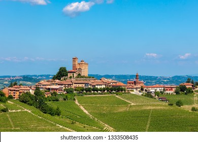 Small medieval twn on the hill with green vineyards under blue sky in Piedmont, Northern Italy.