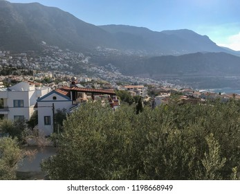 A small Mediterranean town in the rays of the morning sun. Kalkan, Turkey. Town by the sea, surrounded by mountains.