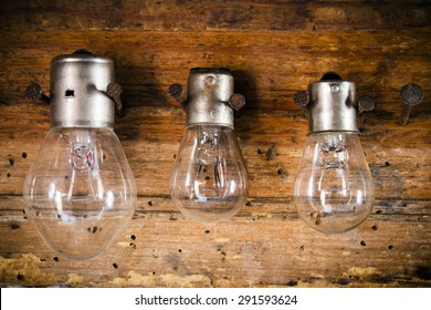 small, medium and large bulbs on the nails on the old wooden stand close up