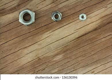 Small Medium Large Nuts on Weathered Wood Background