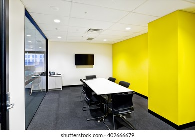 Small meeting room with yellow walls and tv next to glass