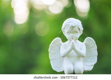 Small memorial angel object in cemetery