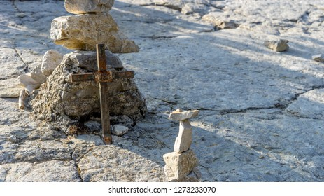 Small metal cross and stacked stones on the pilgrim route to the Montecastello in Italy