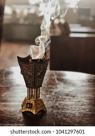 Small metal decorative Arabian Bakhoor incense burner censer with smoke and blurred background.