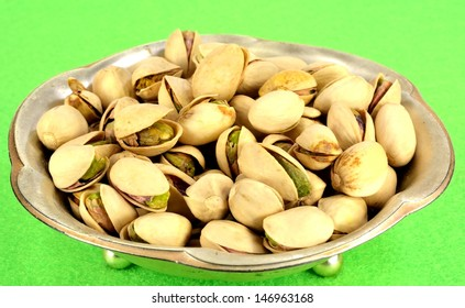 A small metal dish of pistachios in the shell.